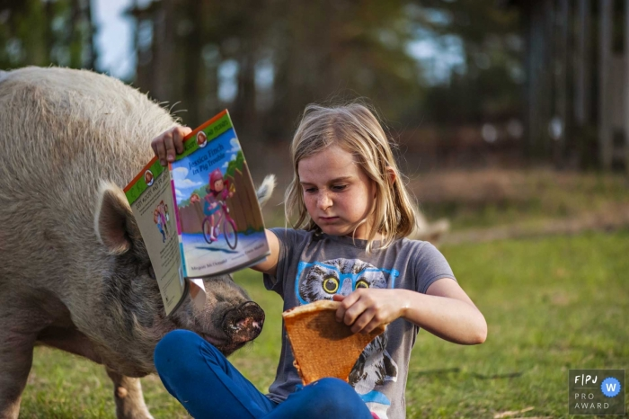 Girl reading a book and eating pizza has an inquisitive pig visitor looking for a snack | North Caroliina Family Photography