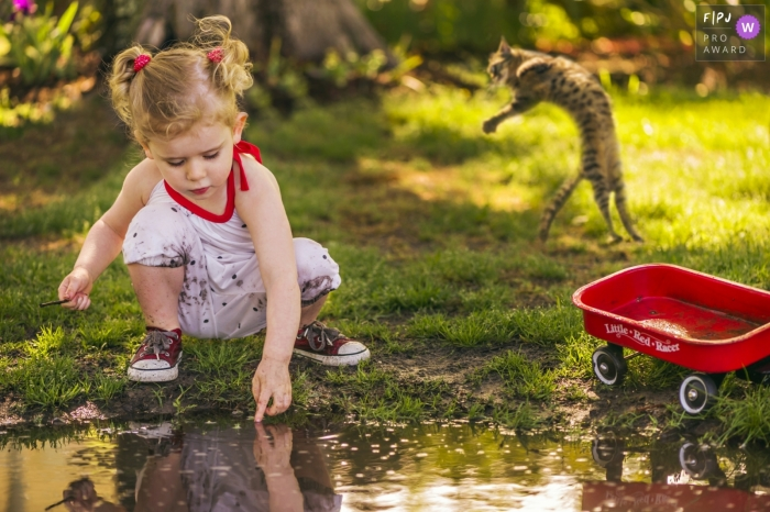Young girl plays in a puddle with her little red wagon and a cat leaping behind her | Outer Banks Family Photography