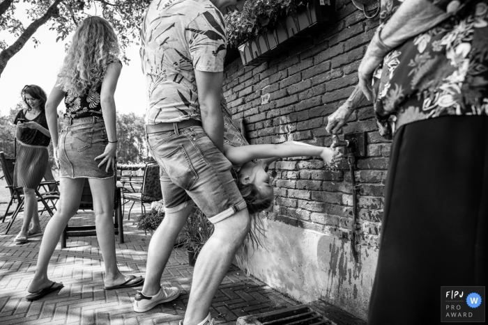 Summer time fun of a girl being held upside down while putting her hand under a water spigot | Gelderland Family Photography