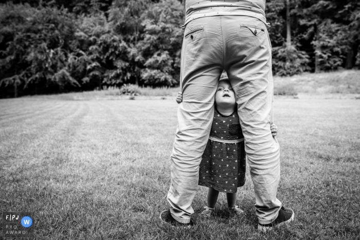 Young girl takes a peak between dad's legs | Gelderland Family Photo