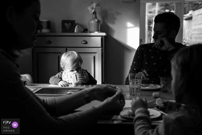 A splash of light falls upon a young child as he take a sip at the table with family   Gelderland Family Session