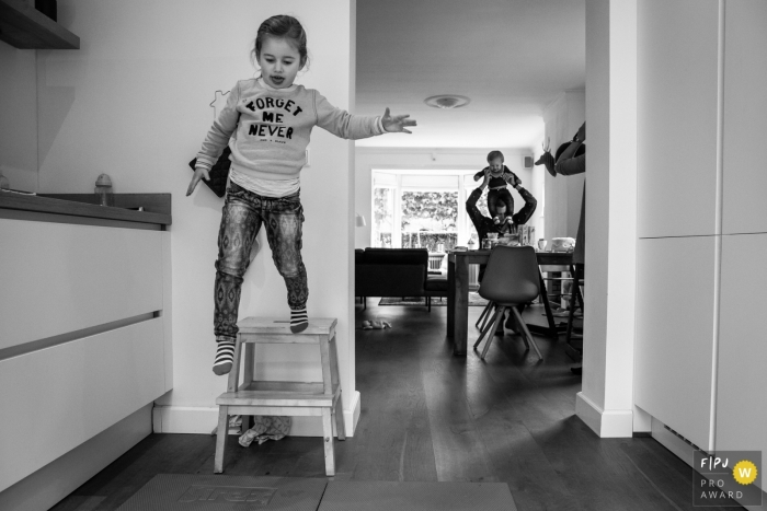 Girl jumps down from a stepping stool at home | Netherlands Family Session