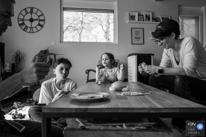 Family sits at the table for a game of cards | Savoie Family Sessions