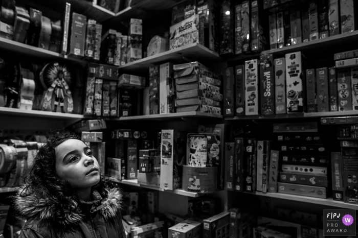 Auvergne-Rhone-Alpes family photo session in town | A girl dreams in a toy store with lots of board games