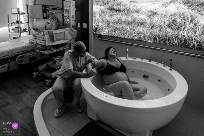Couple hold hands while the woman goes through labor in a bath | Brazil Birthing Photo