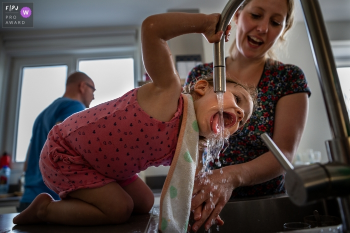 Young girl takes a drink from the kitchen sink   Noord Holland Family Session