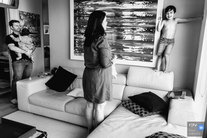 Boy stands on the back of sofa as mom coaxes him to get dressed   Porto Alegre Family Photographer