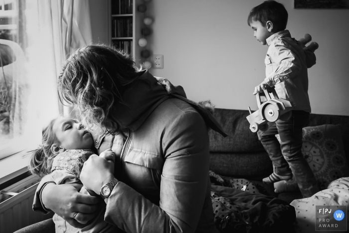 A mother is hugging her child as a young boy walks across the sofa with a toy tractor | Zuid Holland Family Photography