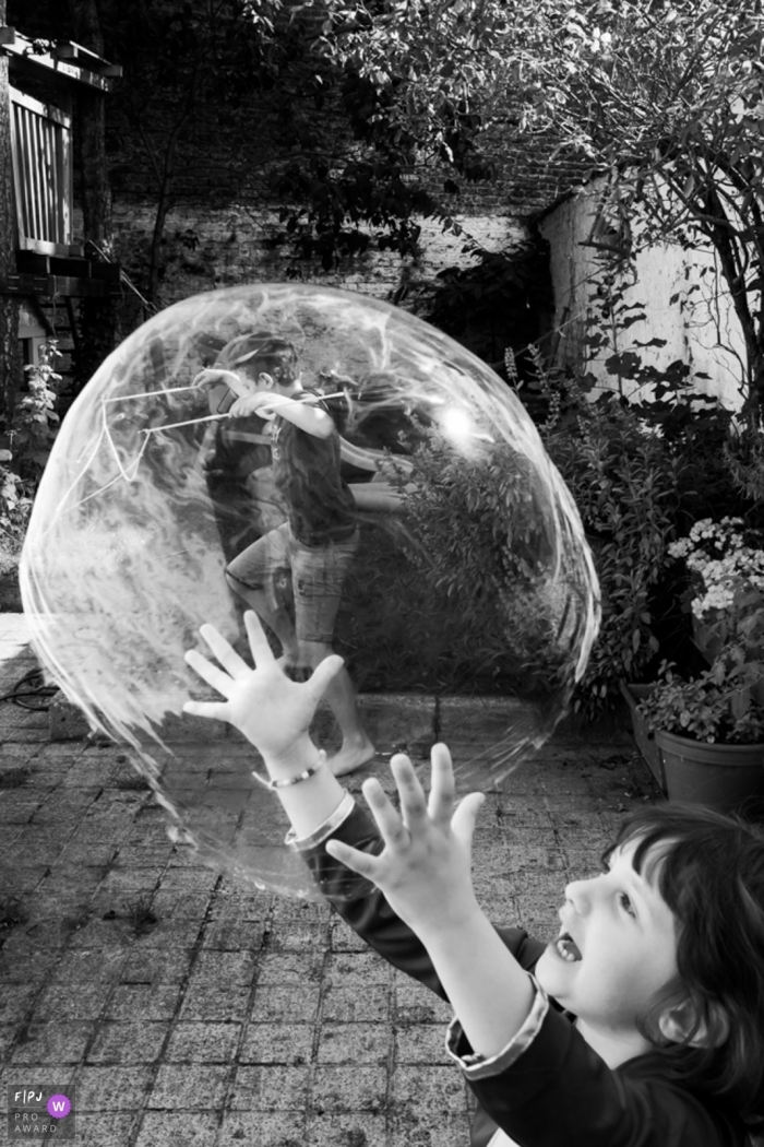 """The """"Bubble Master"""" girl with an oversized bubble, playing in the backyard 
