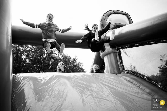 Two kids jump onto a inflated jumbo slide | Belgium children photography