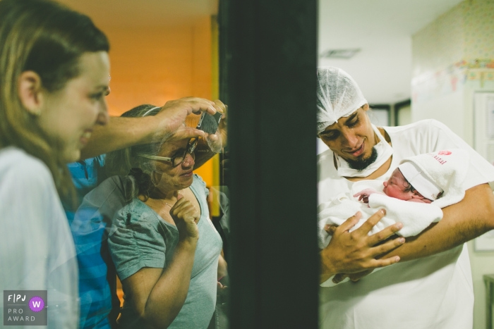 Photo of father showing the newborn son for the first time to the family and everybody is crying | Brazil birth and family photography
