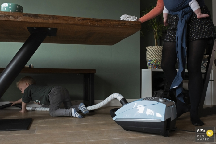 Noord Holland family photos - Vacuuming under and cleaning the kitchen table together