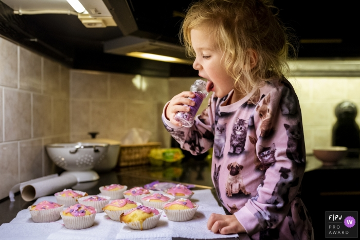 Young girl in the kitchen a jar of sprinkles to her mouth with a spread of cupcakes on the counter before her | Noord Holland Family Session