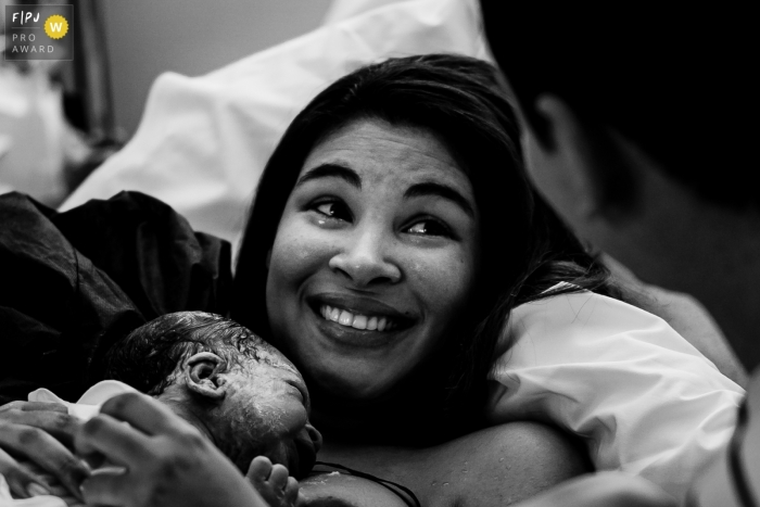 Mother teared up and smiling with her baby after birth | France infant and family photography
