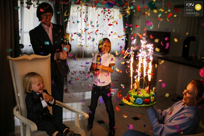 Family celebrates a birthday with a sparkler-lit cake and confetti | Russia party photography