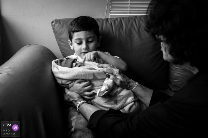 Boy looks over the details of his new sister while sitting on a sofa   Brazil newborn photography
