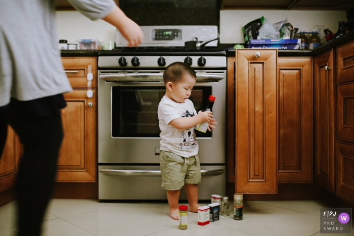 Toddler pulls everything out of the spice cabinet   Los Angeles family photography
