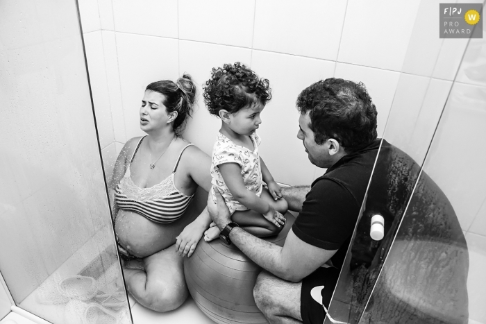 Rio de Janeiro Brazil Pregnant woman in labor in the shower, accompanied by her husband and eldest daughter