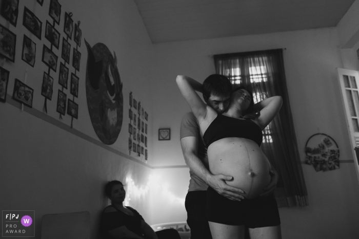 Rio de Janeiro home birthing moment of a husband comforting his wife during labor.