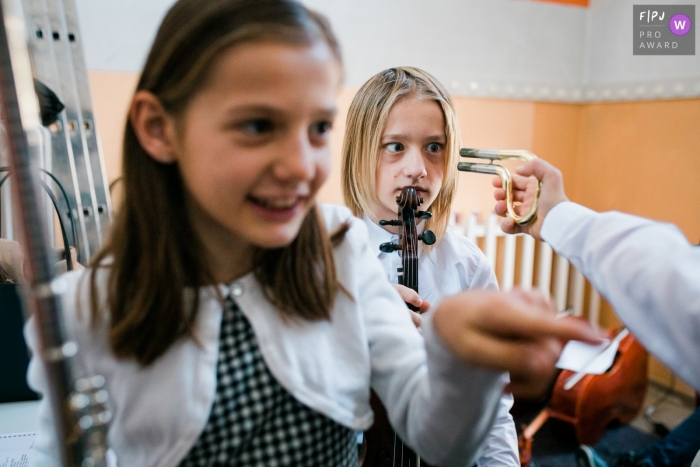 Slovenia kids having fun with instruments while waiting to perform on stage.