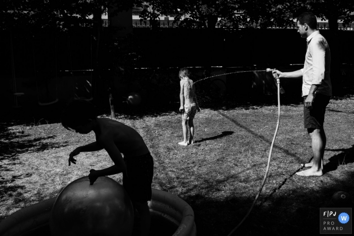 A father spraying his son with water in the backyard during a France family shoot.
