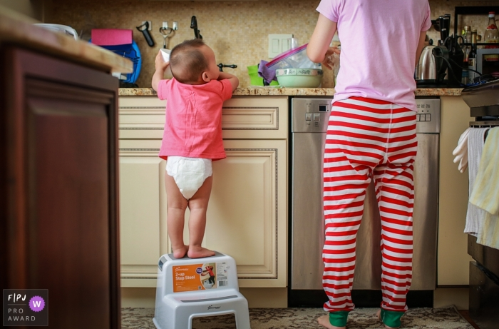 A young child is curious in the kitchen as their parent works on a meal.