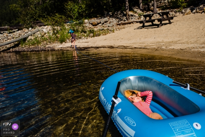 British Columbia girl tows her cousin in rubber dingy at a lakeside beach.