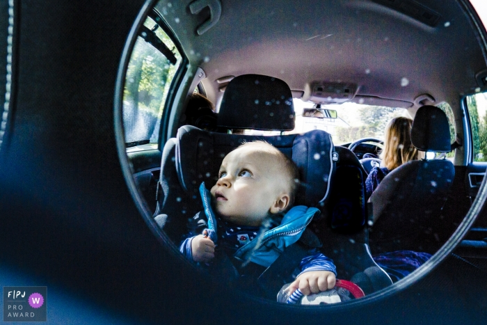 Family reportage Aachen of a reflection of a young child through a fisheye mirror as he sits in his carseat.
