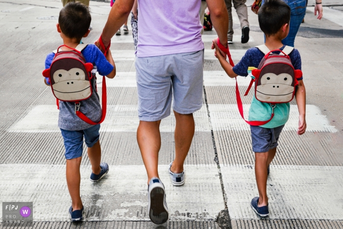 Chicago family of a father holding hands with his two boys with twin monkey backpacks.