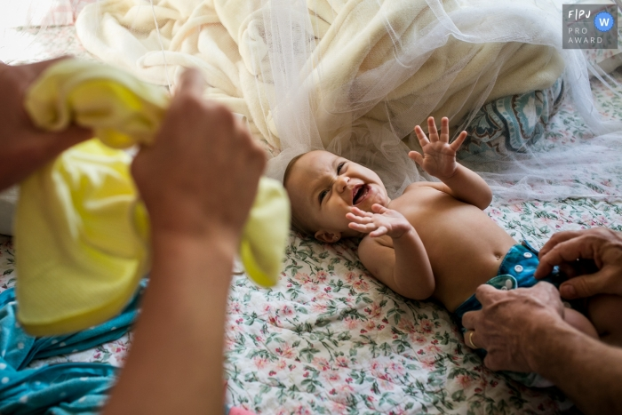 Belo Horizonte Minas Gerais child reacts with joy to parents during a change of clothes