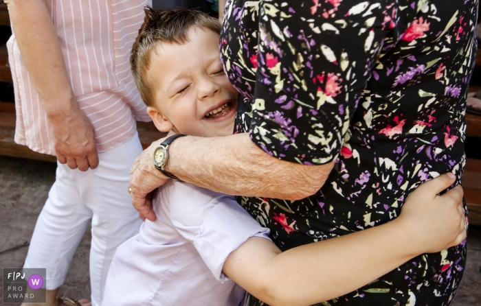 Madison Wisconsin boy takes a moment to hug his Grandmother between family portraits.