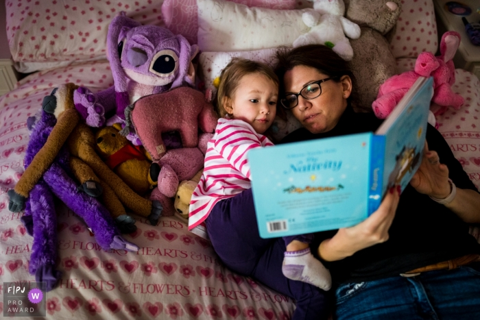 KentEngland mother reads her daughter a bedtime story, surrounded by her special toys