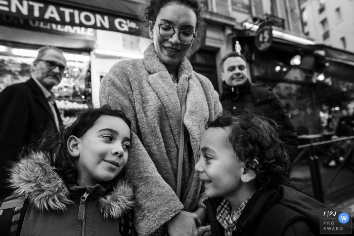 A mom and her 2 children at a Parisian crossroads in France.