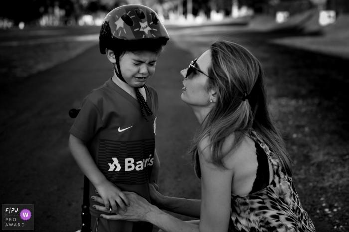 London boy wearing a bicycle helmet is nurtured by his mother.