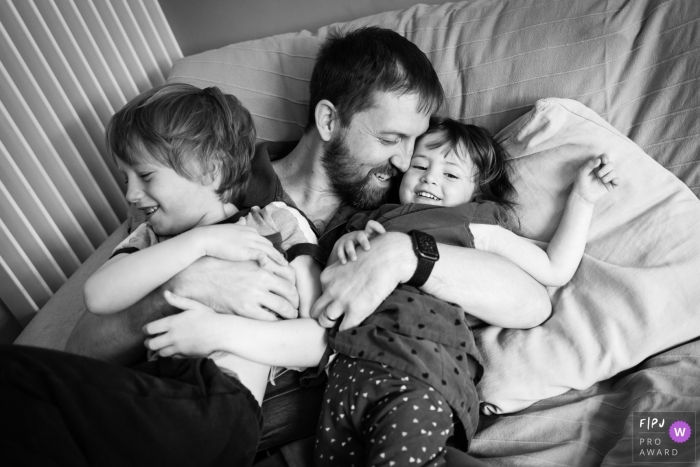 England family photo shoot of a dad cuddling with his children