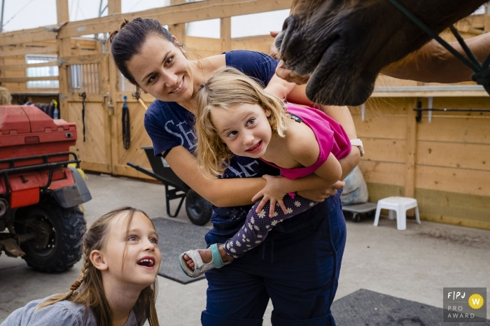 Ontario Canada mom holds daughter while both daughters stretch to look inside horse's mouth