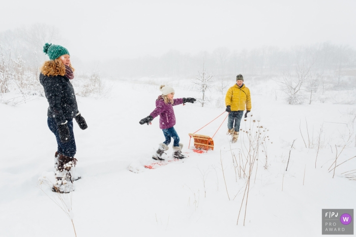 Madison Wisconsin Family of three takes a snowy walk. Girl pretends she's surfing.
