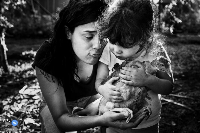 Ribeirao PretoSao Paulo mother and daughter looking after a chicken