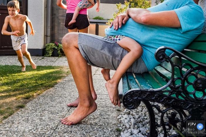 Dusseldorf North Rhine-Westphalia child Hiding under dad on the bench