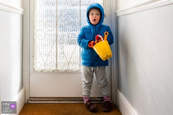 Kent England Little girl waits by the door in big winter coat holding bucket and spade