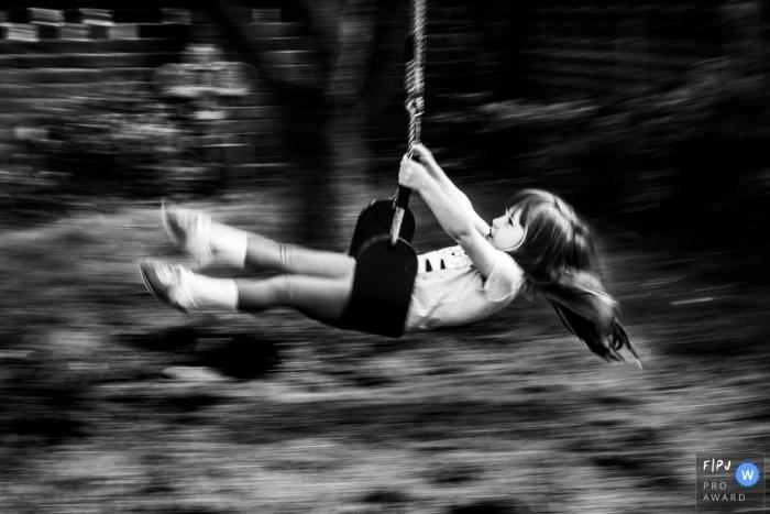 Kent England Little girl plays on swing - slow shutter pan photo