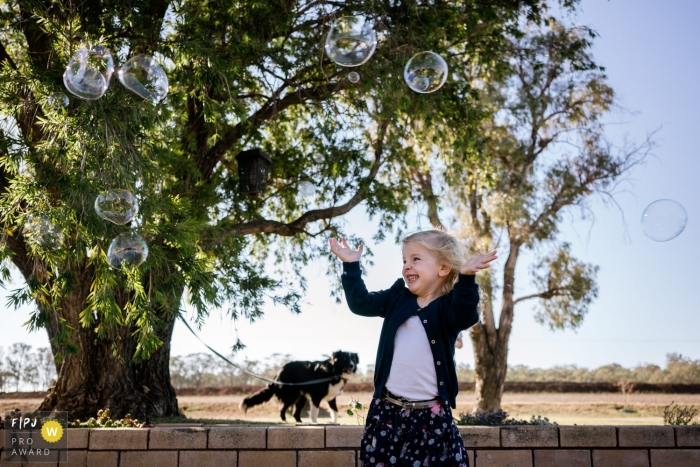 Kent England Little girl surrounded by bubbles outside with her dog