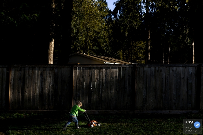 Washington child pretends to mow the lawn in backyard during sunset