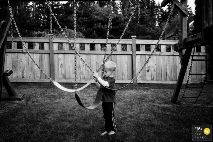Washington kid plays with swings in backyard at home
