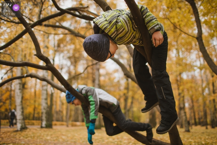 Saint-Petersburg Russia boys climbing trees in the cool fall weather