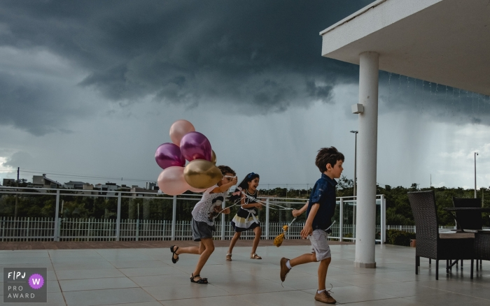 Mato Grasso children run with balloons from a quickly approaching storm.