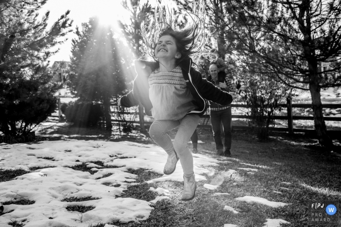 Boulder Colorado girl jumping for joy in the snow with dad in the background laughing