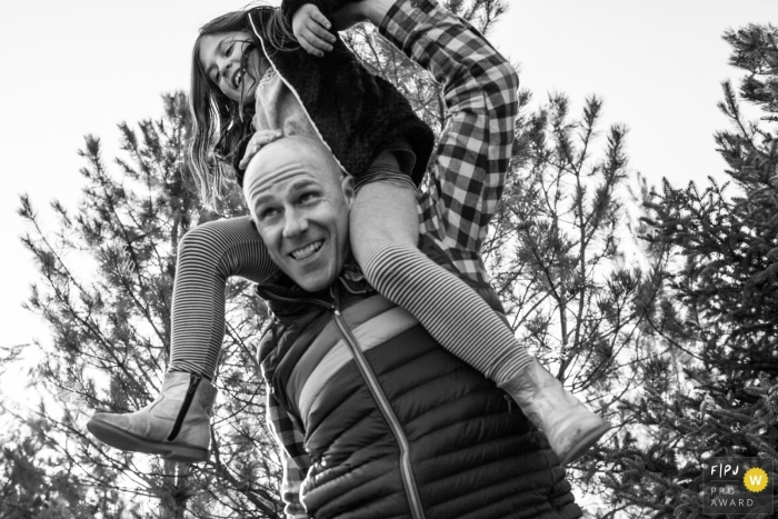 Boulder Colorado dad holding daughter on his shoulders outside under the trees