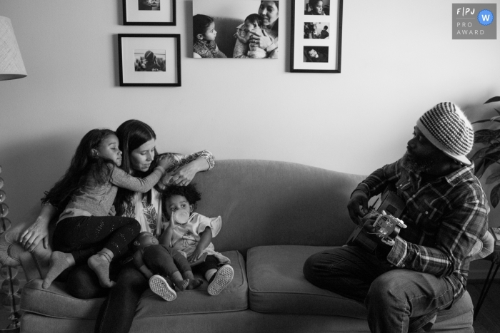 Boulder dad playing guitar, daughter hugging mom, littlest drinking bottle as mom plays with her hair