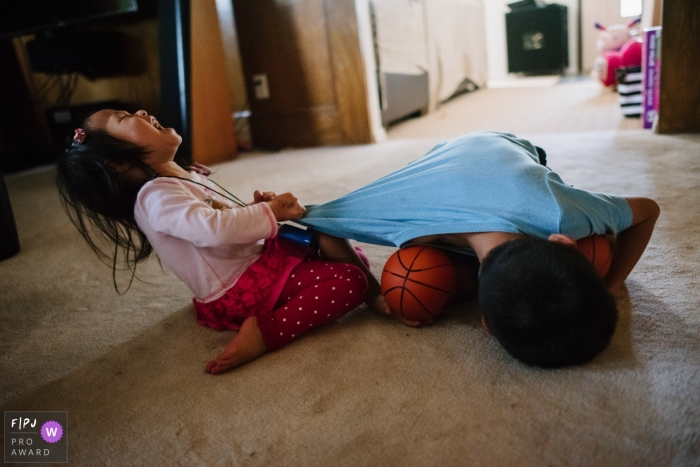 Los Angeles siblings fight and yell as they play with basketballs on the livingroom floor